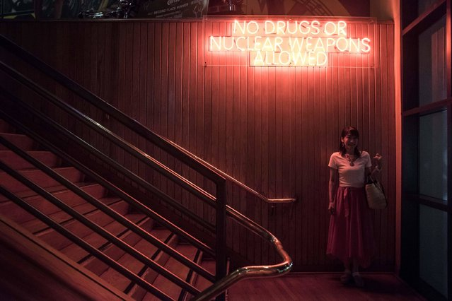 This photograph taken on August 12, 2017, shows a woman posing for a friend beneath a sign reading 'No drugs or nuclear weapons allowed' at the entrance to a restaurant in the Tamuning area of Guam. (Photo by Ed Jones/AFP Photo)