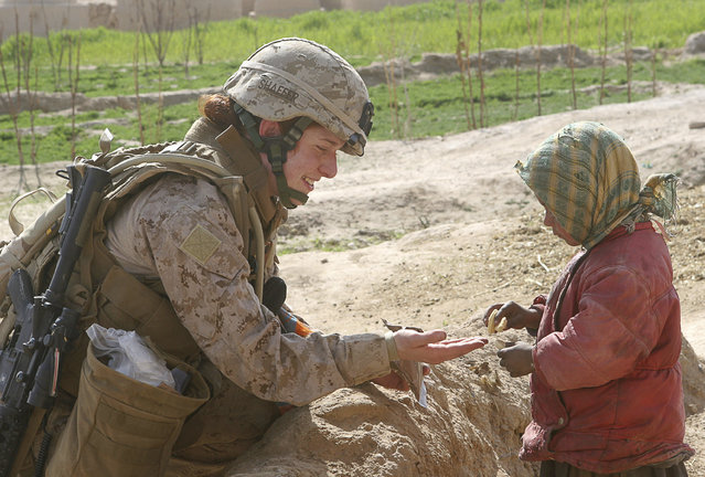 Second Lt. Johanna Shaffer shares a cookie with an Afghan child while under the security of Marines assigned to 3rd Battalion, 8th Marine Regiment (Reinforced), during her all-female team's first mission in Farah Province, February 9, 2009. (Photo by Monty Burton/Reuters/U.S. Marine Corps)