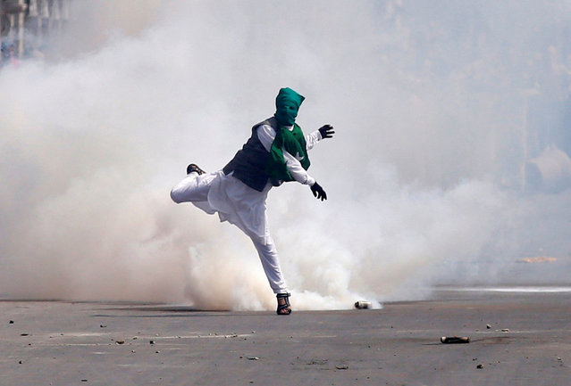 A demonstrator throws stones amid tear gas smoke fired by Indian police during a protest against what protesters say is the house arrest of Kashmiri separatist leaders, after Eid al-Fitr prayers in Srinagar July 6, 2016. (Photo by Danish Ismail/Reuters)