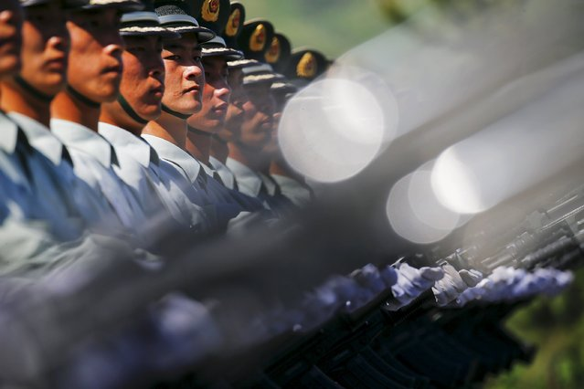 Soldiers of China's People's Liberation Army march with their weapons during a training session for a military parade to mark the 70th anniversary of the end of World War Two, at a military base in Beijing, China, August 22, 2015. (Photo by Damir Sagolj/Reuters)