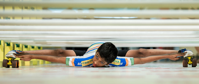 India's Rohan Ajit Kokane, 11, performs in Hong Kong on July 25, 2012, flattening his body until none of it is higher than 6.75 inches off the ground. The event staged in a local shopping mall was aimed at encouraging sport practice among the elderly. (Photo by Philippe Lopez/AFP Photo)