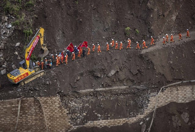 A group of rescue workers walk through a collapsed road at an earthquake hit area in Ludian county, Zhaotong, Yunnan province, August 5, 2014. An earthquake in China on the weekend triggered landslides that have blocked rivers and created rapidly growing bodies of water that could unleash more destruction on survivors of the disaster that killed 410 people, state media reported on Thursday. (Photo by Reuters/Stringer)