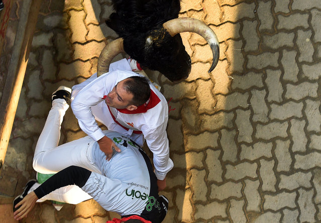 Runners are knocked down by a Pedraza de Yeltes fighting bull near the entrance to the bullring during the fourth running of the bulls at the San Fermin festival in Pamplona, northern Spain, July 10, 2016. (Photo by Eloy Alonso/Reuters)