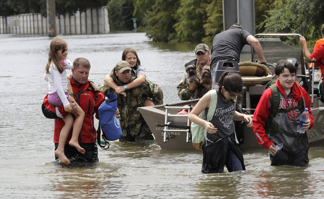 Residents are rescued from their homes surrounded by floodwaters from Tropical Storm Harvey on Sunday, August 27, 2017, in Houston, Texas. (Photo by David J. Phillip/AP Photo)