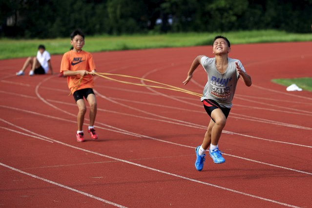 Youths attend a daily track-and-field class, part of a training course at the Jinshan Youth Spare-time Sports School, in Shanghai, August 25, 2015. About 30 youths, between 10 and 14 years old, are enrolled in the course where the top participants will be selected to be groomed to become professional athletes. (Photo by Aly Song/Reuters)