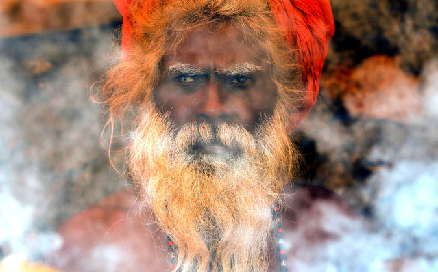 A Naga sadhu, or naked Hindu holy man, performs a ritual inside his tent during Kumbh Mela, or Pitcher festival, at Trimbakeshwar, India, Friday, August 28, 2015. Hindus believe taking a dip in the waters of a holy river during the festival will cleanse them of their sins. The festival is held four times every 12 years. (Photo by Rajanish Kakade/AP Photo)