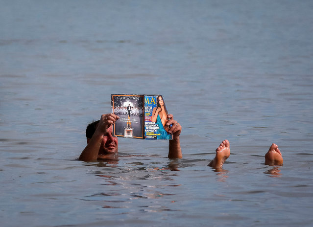 A tourist reads a magazine as he floats in the salt waters of lake Tus in Khakassia region, southwest of the Siberian city of Krasnoyarsk, Russia, July 16, 2016. (Photo by Ilya Naymushin/Reuters)