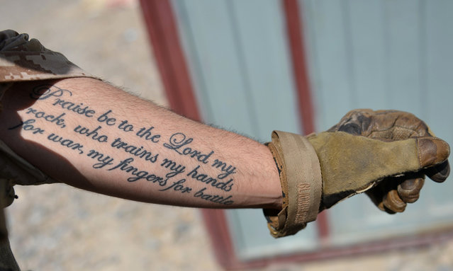 A US Marine from Kilo Company of the 3rd Battalion 8th Marines Regiment shows his tattoo during a patrol in Garmser, Helmand Province, Afghanistan, on June 27, 2012. (Photo by Adek Berry/AFP)