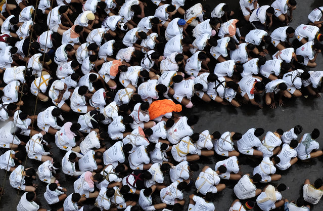 Devotees pray before forming a human pyramid to break a clay pot containing curd during celebrations to mark the Hindu festival of Janmashtami in Mumbai August 18, 2014. Janmashtami, which marks the birthday of Hindu god Krishna, is being celebrated across the country today. (Photo by Danish Siddiqui/Reuters)