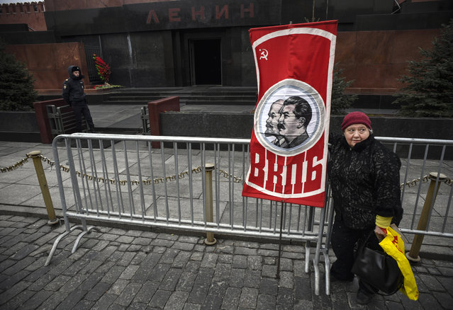A Russian Communist party supporter holds a banner with portraits of Soviet leaders Vladimir Lenin and Joseph Stalin during a memorial ceremony at Stalin's tomb marking the 67th anniversary of his death at Red Square in Moscow on March 5, 2020. While historians blame Stalin for the deaths of millions in purges, prison camps and forced collectivization, many in Russia still praise him for leading the Soviet Union to victory over Nazi Germany in World War II. (Photo by Alexander Nemenov/AFP Photo)