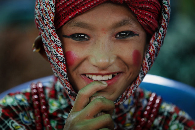 A Nepalese boy gets ready to perform a stick dance during a rally held to pay tribute to the victims of an earthquake, in Bhaktapur, Nepal, Wednesday, September 2, 2015. Two powerful earthquakes in April and May devastated the Himalayan nation killing more than 8,800 people. (Photo by Niranjan Shrestha/AP Photo)