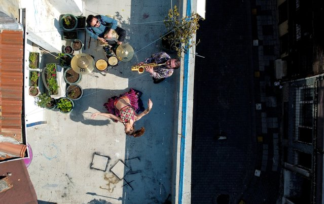 An aerial view of the performance of dancer Su Sevda Uzun from a terrace of her friend's home while she is accompanied by musicians Hakan Kaya and Alper Kalayciklioglu which they organise regularly for their neighbours as the spread of the coronavirus disease (COVID-19) continues in Istanbul, Turkey, April 13, 2020. (Photo by Umit Bektas/Reuters)