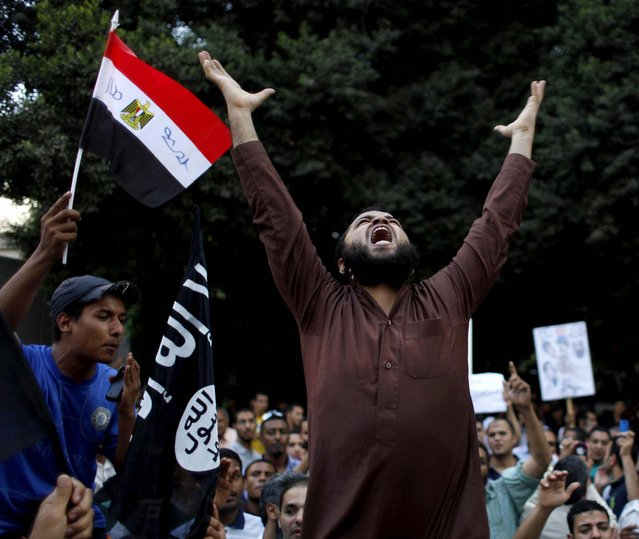 """Protesters carry their national flag and a flag with Arabic that reads """"No God but Allah, and Muhammad is his prophet"""", and chant anti-U.S. slogans during a demonstration in front of the U.S. embassy in Cairo, Egypt, as part of widespread anger across the Muslim world about a film ridiculing Islam's Prophet Muhammad. (Photo by Nasser Nasser/Associated Press)"""