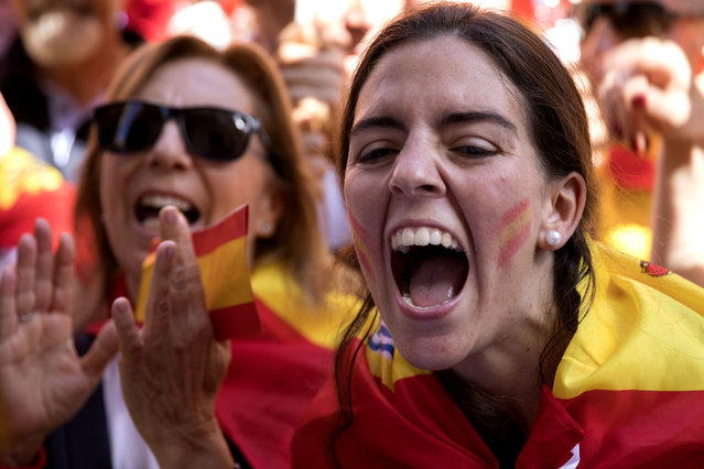 Demonstrators shout slogans as thousands of people march to protest the Catalan government's push for secession from the rest of Spain in downtown Barcelona, Spain, Sunday October 8, 2017. Sunday's rally comes a week after separatist leaders of the Catalan government held a referendum on secession that Spain's top court had suspended and the Spanish government said was illegal. (Photo by Emilio Morenatti/AP Photo)
