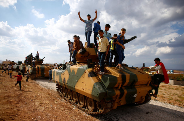 Boys stand on top of a Turkish army vehicle as a military convoy pass by their village on the Turkish-Syrian border line in Reyhanli, Hatay province, Turkey, October 11, 2017. (Photo by Osman Orsal/Reuters)