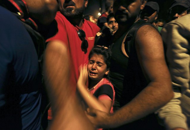 A Syrian refugee child cries as she is squeezed by other refugees and migrants trying to move ahead at Geece's border with Macedonia near the village of Idomeni early morning September 7, 2015. Thousands of migrants and refugees were crowding at Greece's border with Macedonia on Monday morning, their entry slowly rationed by Greek and Macedonian police. (Photo by Yannis Behrakis/Reuters)