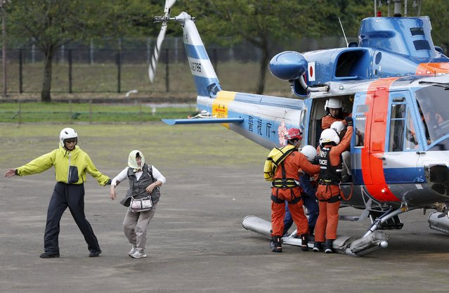 A woman (2nd L) walks with a rescue worker after being rescued by a helicopter from an area flooded by the Kinugawa river, caused by typhoon Etau, upon their arrival at Ishige Sports Park acting as an evacuation center in Joso, Ibaraki prefecture, Japan, September 10, 2015. (Photo by Issei Kato/Reuters)