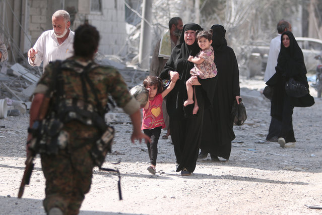 A Syria Democratic Forces (SDF) fighter rushes to help civilians who were evacuated by the SDF from an Islamic State-controlled neighbourhood of Manbij, in Aleppo Governorate, Syria, August 12, 2016. (Photo by Rodi Said/Reuters)