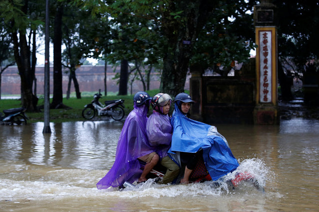 People ride a motorcycle along flooded road after typhoon Damrey hits Vietnam in Hue city on November 5, 2017. (Photo by Reuters/Kham)