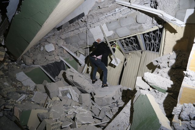 Iraqis search for the trapped citizens over the collapsed buildings after a 7.3 magnitude earthquake hit northern Iraq in Derbendihan district of  Sulaymaniyah, Iraq on November 12, 2017. An earthquake measuring 7.3 on the Richter scale rocked northern Iraq and Iran, the U.S. Geological Survey said on Sunday evening. At least 61 people were killed and more than 300 others injured in Iran's border areas, according to information provided by the concerned authorities, said Iran's semi-official Fars News Agency. (Photo by Feriq Fereçc/Anadolu Agency/Getty Images)