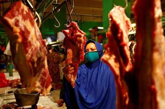 A woman wears a protective face mask as she buys meat for making traditional food ahead of Eid al-Fitr celebrations at the traditional market in Jakarta, Indonesia, May 22, 2020. (Photo by Ajeng Dinar Ulfiana/Reuters)