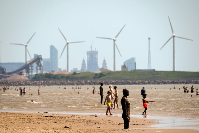 People enjoy the warm weather on Crosby Beach on June 25, 2020 in Liverpool, United Kingdom. The UK is experiencing a summer heatwave, with temperatures in many parts of the country expected to rise above 30C and weather warnings in place for thunderstorms at the end of the week. (Photo by Christopher Furlong/Getty Images)
