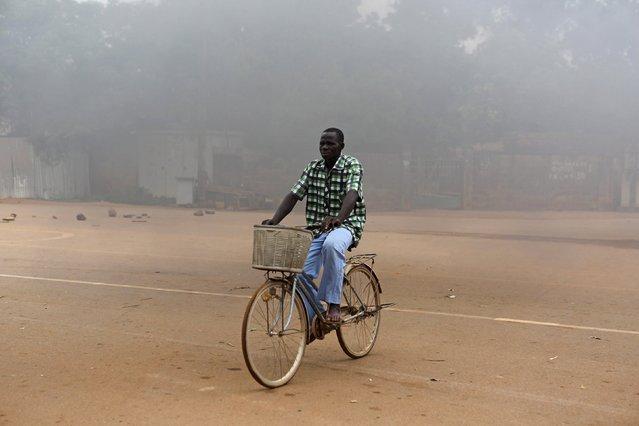 A man on a bicycle rides past a burning roadblock in Ouagadougou, Burkina Faso, September 18, 2015. (Photo by Joe Penney/Reuters)
