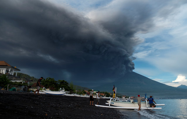 Indonesia's Mount Agung volcano erupts as fishermen pull a boat onto the beach in Amed, Bali, Indonesia, November 26, 2017. (Photo by Petra Simkova/Reuters)