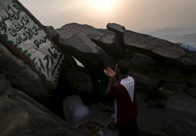 A Muslim pilgrim prays as he stands in front of Hera cave, where Muslims believe Prophet Mohammad received the first words of the Koran through Gabriel, at the top of Mount Al-Noor during the annual haj pilgrimage in the holy city of Mecca, September 21, 2015. (Photo by Ahmad Masood/Reuters)