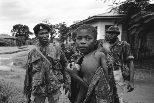An Ibo woman refugee, carrying her dead child over her shoulder, appears not to notice the shouts of Federal Nigerian soldier telling her to get to the camp for refugees, as she walks through street after Owerri had fallen to federal troops over the weekend, September 23, 1968. (Photo by Dennis Lee Royle/AP Photo)