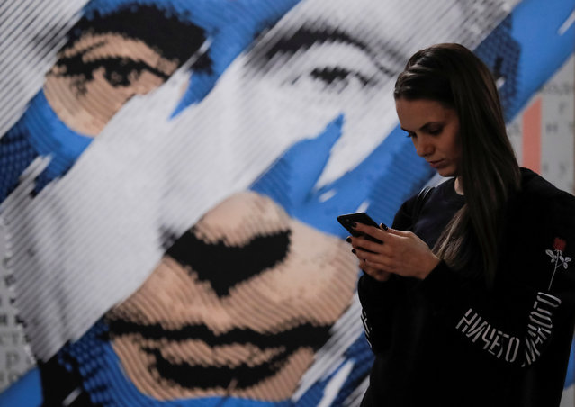 """A woman looks at a mobile phone as she stands in front of a painting depicting Russian president Vladimir Putin at the """"SUPERPUTIN"""" exhibition at UMAM museum in Moscow, Russia on December 6, 2017. (Photo by Maxim Shemetov/Reuters)"""