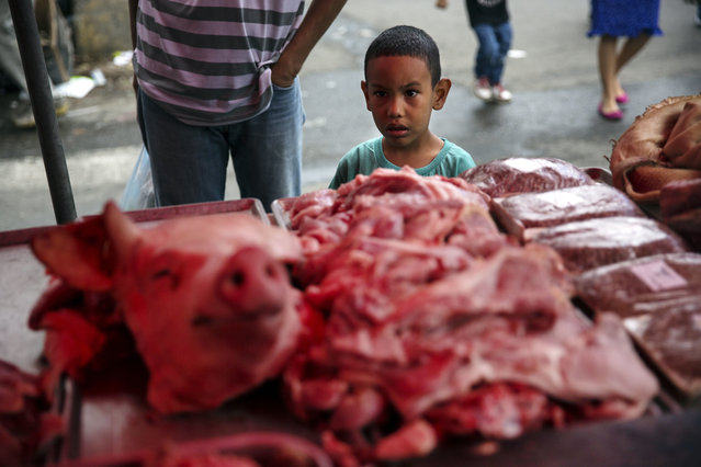 A boy looks at a butcher's stand at a street market downtown in Caracas, Venezuela, Saturday, October 21, 2017. (Photo by Rodrigo Abd/AP Photo)