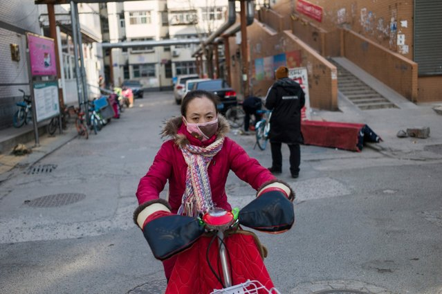 In this picture taken on December 13, 2017, a woman commutes on a street on a cold day in Baoding. As temperatures dipped below freezing in a northern Chinese village, a group of parka-clad women tried to stay warm as they played mahjong around a small gas stove in a grocery store. (Photo by Fred Dufour/AFP Photo)