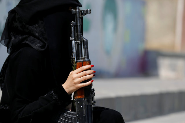 A woman loyal to the Houthi movement holds a rifle as she takes part in a parade to show support to the movement in Sanaa, Yemen September 6, 2016. Dressed in the head to toe garments which obscured their faces, the female fighters brandished machine guns, rocket launchers and grenades. The women also wore hats as they showed support for the Shiite Houthi rebels. The Saudi-led Arab coalition launched a military campaign against the Houthis and their allies in March 2015. It was after the rebels closed in on Gulf-backed President Abedrabbo Mansour Hadi in his southern refuge of Aden, forcing him into exile. The female protesters have pledged to remain supportive and do whatever they can to back the ongoing resistance against the kingdom. Yemen is in the grip of its most severe crisis in years, and is on the brink of civil war. (Photo by Khaled Abdullah/Reuters)