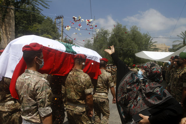 A woman throws flowers over Lebanese army soldiers who carry the coffin of lieutenant Ayman Noureddine, who was killed by Tuesday's explosion that hit the seaport of Beirut, during his funeral procession, in Numeiriyeh village, south Lebanon, Friday, August 7, 2020. Rescue teams were still searching the rubble of Beirut's port for bodies on Friday, nearly three days after a massive explosion sent a wave of destruction through Lebanon's capital. (Photo by Mohammed Zaatari/AP Photo)
