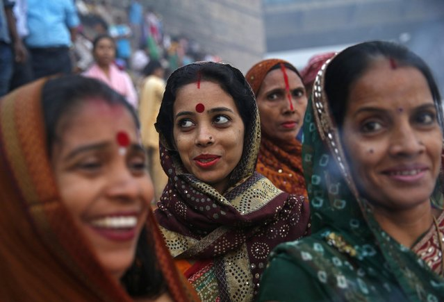 Hindu women smile as they worship the Sun god Surya on the banks of the river Yamuna during the Hindu religious festival of Chatt Puja in New Delhi October 30, 2014. (Photo by Ahmad Masood/Reuters)