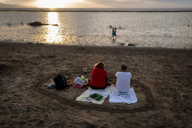 A couple sit at the beach during sunset on the Spanish Gran Canaria island, Spain, Tuesday, August 18, 2020. Spanish authorities have announced new restrictions to help prevent the spreading of COVID-19. (Photo by Emilio Morenatti/AP Photo)