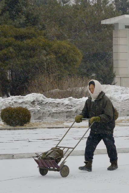 A local pushes a load while dressed in warm clothes in February 2013, in Pyongyang, North Korea. (Photo by Andrew Macleod/Barcroft Media)