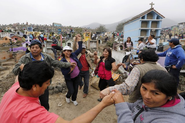 """Members of a family dance at the tomb of a relative at the """"Nueva Esperanza"""" (New Hope) cemetery during the Day of the Dead celebrations on the outskirts of Lima November 1, 2014. Thousands of people visit cemeteries during the annual holiday in Peru to honour the dead. (Photo by Mariana Bazo/Reuters)"""