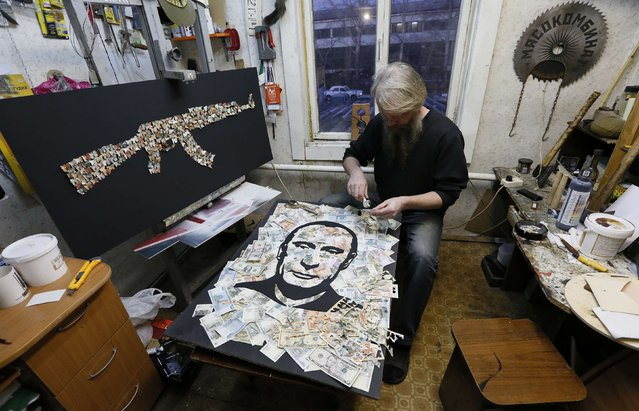 Russian artist Vasily Slonov works with a banknote as he creates an artwork depicting a portrait of Russian President Vladimir Putin based on a layer of U.S. dollars, Russian and Soviet roubles at his workshop in Krasnoyarsk, Siberia, November 13, 2014. (Photo by Ilya Naymushin/Reuters)