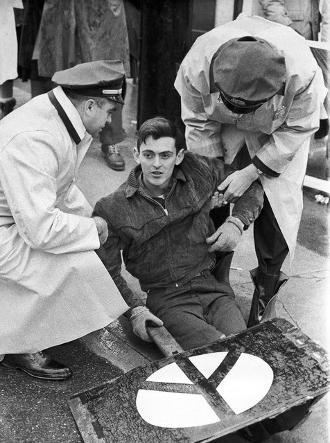 In this January 12, 1963 file photo, demonstrator Michael Kirby, 25, of Milton, Mass., carrying a peace sign, is taken into custody by police in Groton, Conn., outside the launching site of the Polaris nuclear missile submarine USS Nathan Hale. Kirby, a former nuclear weapons specialist in the Navy, was one two pacifists arrested at the site. (Photo by AFP Photo)