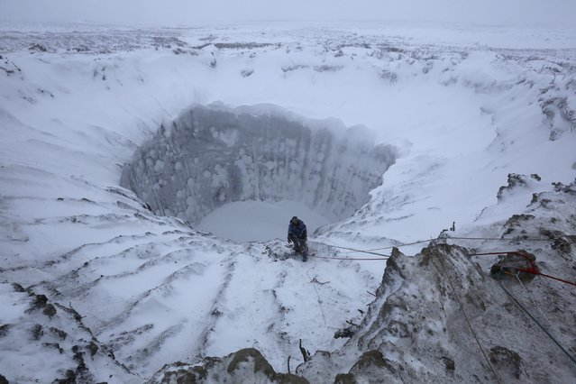 A member of an expedition group stands on the edge of a newly formed crater on the Yamal Peninsula, northern Siberia November 9, 2014. (Photo by Vladimir Pushkarev/Reuters/Russian Centre of Arctic Exploration)