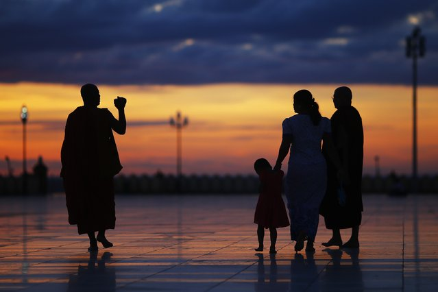 A Buddhist monk films with a camera as people visit Uppatasanti Pagoda in Naypyitaw during sunset November 9, 2014. (Photo by Damir Sagolj/Reuters)