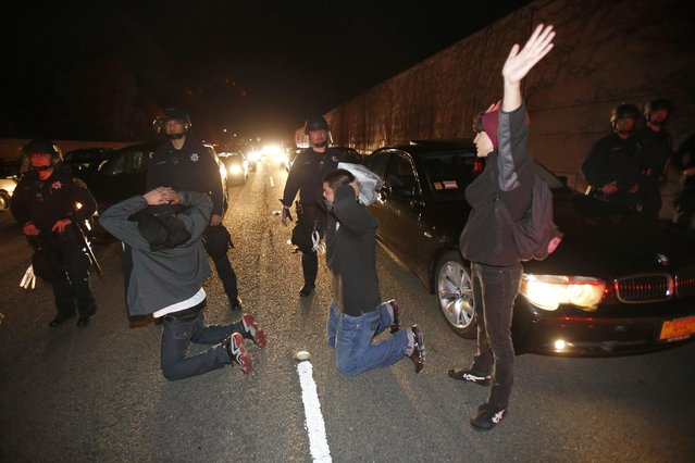 A group of demonstrators raise their hands in front of a line of police officers on Highway 580 during a demonstration, following the grand jury decision in the Ferguson, Missouri shooting of Michael Brown, in Oakland, California November 24, 2014. (Photo by Stephen Lam/Reuters)