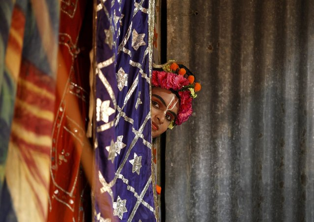An artist peeps out from behind a curtain as he waits backstage to take part in the Ramlila performance, a re-enactment of the life of Hindu Lord Rama, ahead of Dussehra in Ahmedabad, India, October 19, 2015. (Photo by Amit Dave/Reuters)