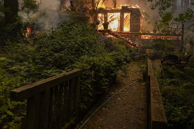 A home burns as the CZU August Lightning Complex Fire passes by, Thursday, August 20, 2020, in Ben Lomond, Calif. (Photo by Marcio Jose Sanchez/AP Photo)