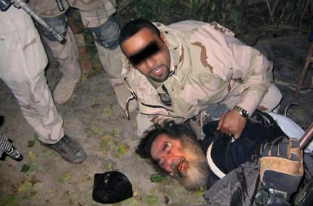 This unsourced picture shows ousted Iraqi leader Saddam Hussein being dragged from hiding following his capture by US troops, on December 13, 2003 in an underground hole at a farm in the village of ad-Dawr, near his hometown of Tikrit in northern Iraq. The picture is one of a series of images of the deposed dictator unauthorized for release by the US army that has been circulating in recent days on the internet. The man holding him was later identified as an Iraqi-American named Samir, who was the translator for the U.S. Special Forces that helped find Hussein. (Photo by AFP Photo/The Atlantic)