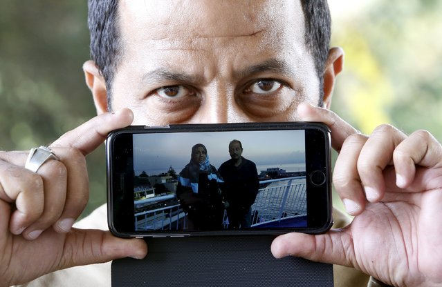 Migrant Abdullah from Baghdad, Iraq, shows a picture of him with his wife as he waits to cross the Slovenia-Austria border in Sentilj, Slovenia October 25, 2015. (Photo by Srdjan Zivulovic/Reuters)