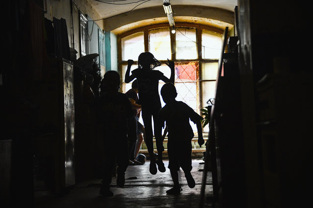 Children play in a communal corridor in a dormitory for the workers of Proletarka textile factory in the town of Tver, 200 kilometres north-west from Moscow on August 8, 2020. The golden age of Proletarka, the unique set of barracks, some fifty neo-Gothic buildings, including two decorated with gold medals at the Universal Exhibition of 1900 in Paris, ended with the break-up of the USSR in 1991 and the arrival of the market economy which opened the borders to inexpensive Chinese textiles. The famous Tver factory, created by cotton magnates Morozov, in 19th century, no longer existed, and its unique city, still overpopulated, was forgotten by the new authorities and turned into a dirty poor ghetto. (Photo by Andrey Borodulin/AFP Photo)