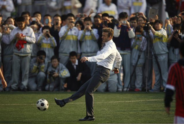 Students take pictures of former England captain David Beckham as he kicks a ball in the field of a middle school during his visit in Beijing March 20, 2013. Beckham arrived in the Chinese capital city on Wednesday to begin his role as China's soccer envoy, according to local reports. (Photo by Petar Kujundzic/Reuters)